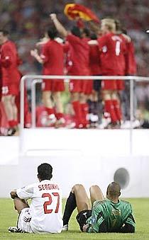 Hai cầu thủ Milan ngồi nhìn Liverpool nâng Cup.
