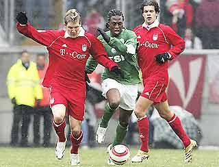 Schweinsteiger (trái) khống chế bóng trước một cầu thủ Wolfsburg.