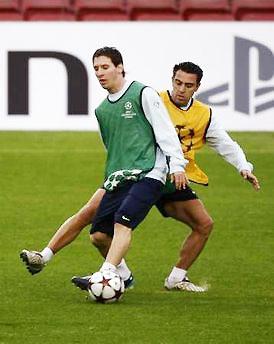 Xavi tranh bóng bới Messi trên sân tập.