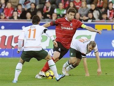 Heiko Butscher của Freiburg đối phó với cặp tiền vệ Bremen, Ozil và Jensen.