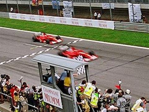 Barrichello (trái) giảm tốc độ nhường Schumi khi chặng đua chỉ còn vài giây.