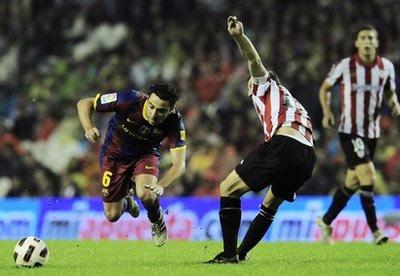 Xavi tranh bóng với tiền vệ Gurpegi (Bilbao).