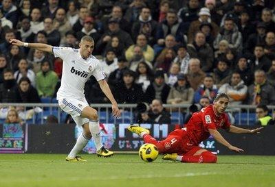 Tiền đạo Benzema của Real tranh bóng với Martin Caceres của Sevilla.