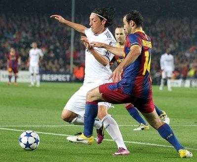 Ozil (bên trái) tranh bóng với Mascherano của Barca trong trận bán kết Champions League.