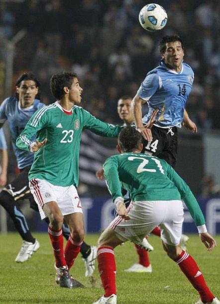 Uruguay (áo xanh nhạt) gây sức ép trước hàng thủ Mexico.