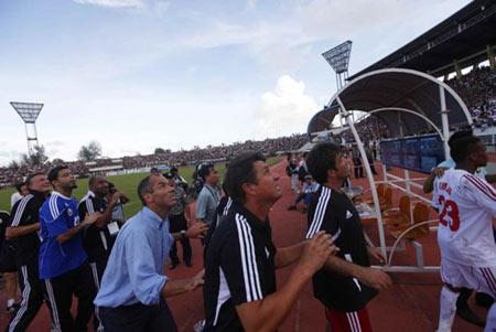 Cầu thủ và ban huấn luyện Oman vừa chạy vừa nhìn lên khán đài để né