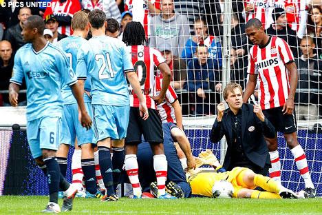 Tyton bất tỉnh sau khi lĩnh trọn cú húc đầu gối của đồng đội và được nẹp cổ để đưa đi cấp cứu. Ảnh: PSV Pics.
