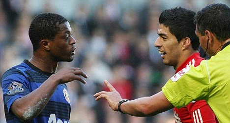 Evra (trái) và Suarez trong một lần bị trọng tài nhắc nhở.