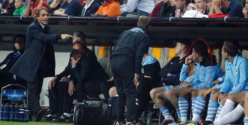 HLV Mancini (trái) tức giận khi Tevez (vòng đỏ) từ chối đề nghị của ông về việc khởi động để vào thay người.