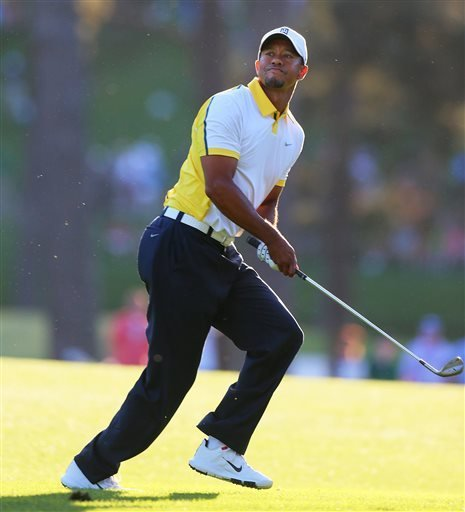Golfer Tiger Woods reacts to his recovery shot from off the fairway over the trees to the 17th green during the second round in the Masters golf tournament on Friday, April 12, 2013, in Augusta, Ga