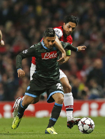Arsenal's Mikel Arteta, rear, challenges Napoli's Lorenzo Insigne during the Champions League Group F soccer match between Arsenal and Napoli at the Emirates Stadium in London, Tuesday, Oct. 1, 2013