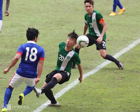 Tiền vệ Malaysia Azwari thực hiện pha qua người với hậu vệ Macau. Ảnh: Đức Đồng.