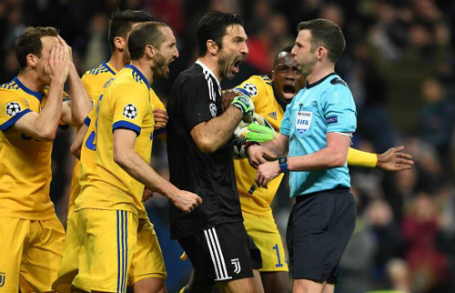 Buffon và cầu thủ Juventus phản đối trọng tài Oliver. Ảnh:Reuters.