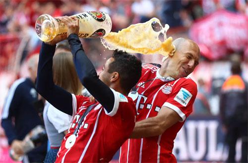 Dàn cầu thủ Bayern mở tiệc mừng chức vô địch Bundesliga sau trận đấu. Ảnh:AFP.