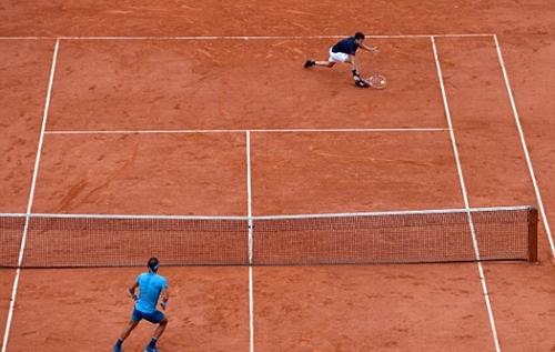 Nadal chủ động lên lưới sau một pha ép trái Thiem. Ảnh: AFP.
