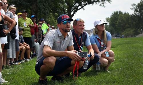 Phelps (ngồi bên trái)đến CLB golf Bellerive từ tối thứ Bảy, trước khi dành trọn ngày Chủ nhật để cổ vũ Tiger Woods. Ảnh: Evening Standard.