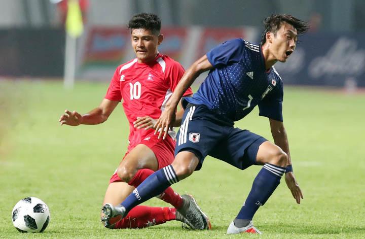 Nepal (áo đỏ) chơi phòng ngự chặt chẽ trong trận thua Olympic Nhật Bản 0-1 tối 14/8. Ảnh: Đức Đồng