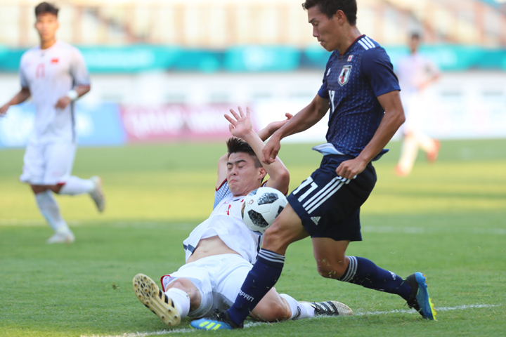 Duy Mạnh truy cản một pha tấn công của Nhật Bản, trong chiến thắng 1-0 ở lượt trận cuối cùng bảng D hôm qua. Ảnh: Đức Đồng.