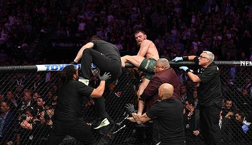 Chứng kiến Khabib hành hung người của đội mình, McGregor cũng định lao vào ẩu đả. Nhưng do thấm mệt vì bị đánh trong bốn hiệp, võ sĩ người Ireland bị cản lại. Ảnh: AP.