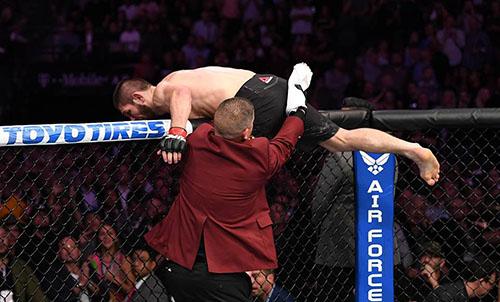 Khabib trèo khỏi lồng bát giác, ngay sau khi trận đấu giữa anh và McGregor kết thúc, bất chấp sự ngăn cản của mọi người. Ảnh: LLC.