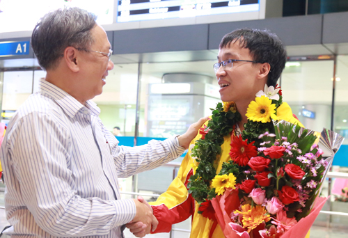 Trường Sơn (phải) nhận hoa chúc mừng từ ông Mai Bá Hùng - Giám đốcSở Thể dục Thể thaoTP HCM, khi trở về nước tối 8/10.