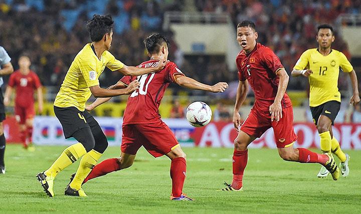 Việt Nam sau khi dẫn bàn sớm đã chơi với đội hình thấp. Ngay cả tiền đạo Anh Đức (phải) cũng thường xuyên lùi về hỗ trợ cho đồng đội. Ảnh: Giang Huy.