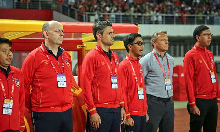 HLV Antoine Hey (áo sơ mi sáng màu) cùng Ban huấn luyện đội tuyển Myanmar. Ảnh: Reuters.