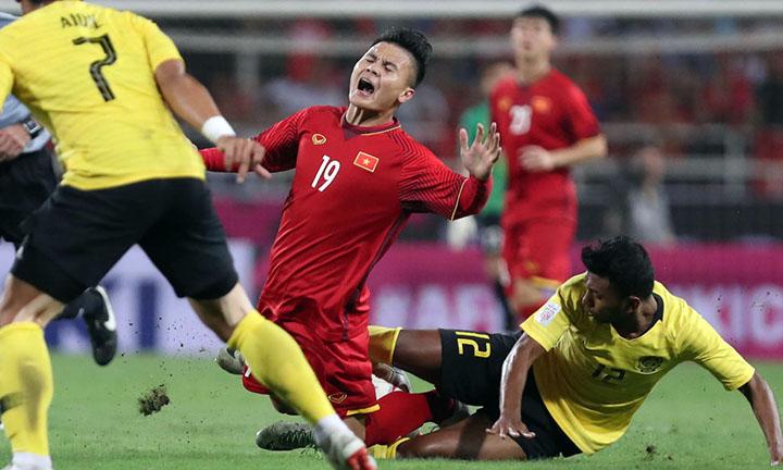 Việt Nam (áo đỏ) từng gặp nhiều khó khăn trước lối chơi áp sát, rắn, và có phần thô bạo của Malaysia tối 16/11. Ảnh: Đức Đồng.