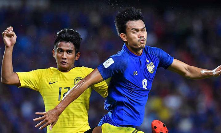 Irfan (áo vàng) theo kèm tiền đạo Adisak ở bán kết AFF Cup. Ảnh: AFF.
