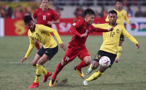 Quang Hải (đỏ) đi bóng qua các cầu thủ Malaysia ở chung kết lượt về tại Mỹ Đình.
