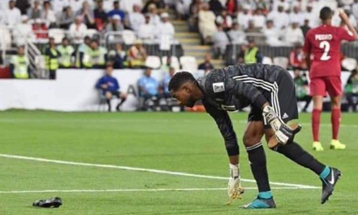 Thủ môn UAE nhặt đồ đạc, giày dép của CĐV ném xuống sân. Ảnh:AFC.