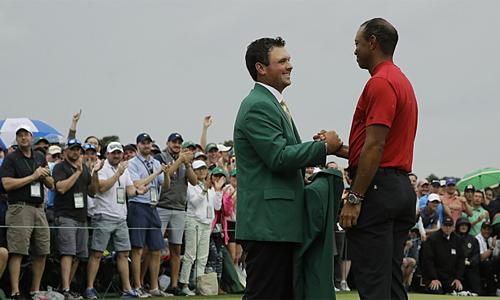 Woods (phải) nhận Áo Xanh từ nhà vô địch năm 2018, Patrick Reed. Ảnh: AP.