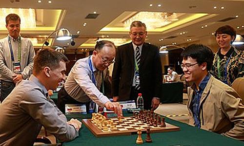 Quang Liêm (ngồi bên phải) gặp hạt giống số một Andreikin ở ván đầu cờ chớp. Ảnh: IMSA.