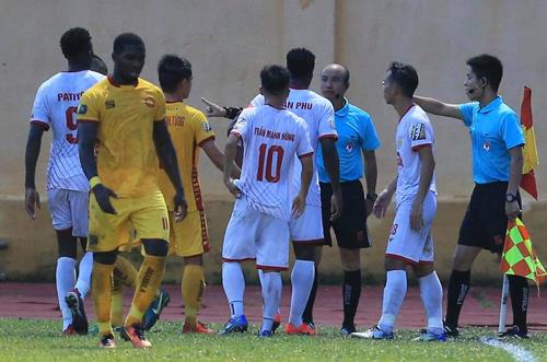 Cầu thủ Nam Định vây quanh phản ứng với quyết định không công nhận bàn thắng của trọng tài Ngô Quốc Hưng.
