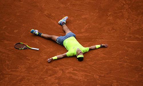 Nadal nằm sân mừng chiến thắng thứ 12 ở Roland Garros. Ảnh: Reuters.
