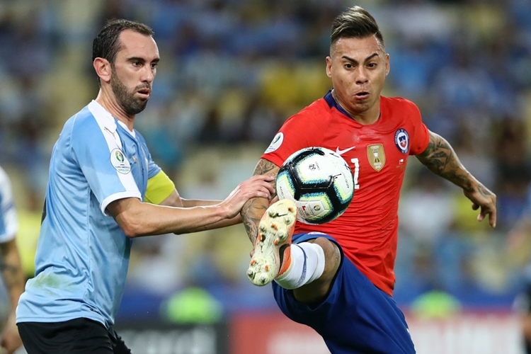 Godin (trái) không những khóa chặt tiền đạo Vargas mà còn rất nguy hiểm khi lên tấn công. Ảnh: Goal.