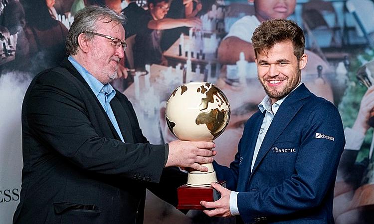 Carlsen (phải)nhận cup vô địch. Anh được kỳ vọng chạm mốc Elo 2.900 trong thời gian tới. Ảnh: Lennart Ootes.
