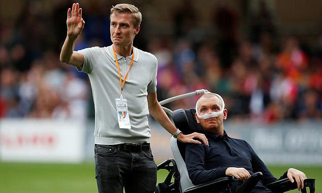 Stephen Darby (phải) ngồi xe lăn tiến ra sân chào khán giả. Ảnh: PA.