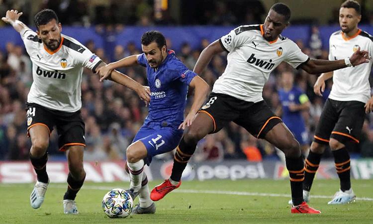 Pedro giữa vòng vây của các hậu vệ cao to phía Valencia. Ảnh: AP.