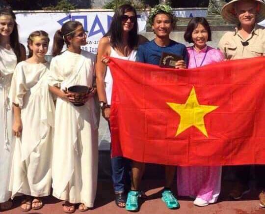 Quang Trần (đeo vòng nguyệt quế) tự vào khoe quốc kỳ Việt Nam sau khi về đích và được ban tổ chức Spartathlon chào đón, dưới chân bức tượng Leonidas I. Ảnh: NVCC.