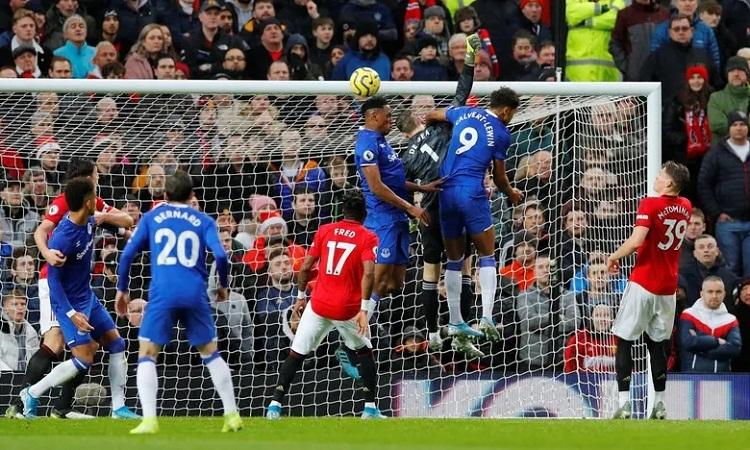 Calvert-Lewin không bị phạt dù dùng tay đè De Gea khi nhảy lên tranh chấp. Ảnh: Reuters.