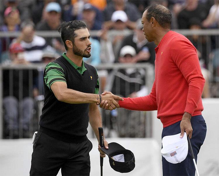 Woods bắt tay Ancer (trái) sau khi thắng golfer Mexico trong trận đánh đơn đối kháng đầu tiên của ngày thi đấu cuối cùng hôm nay 15/12. Ảnh: AP.