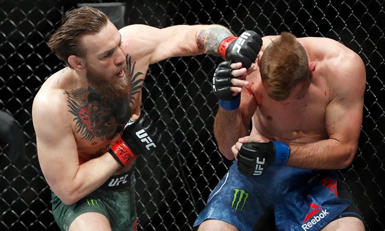 McGregor (trái) tấn công dồn dập và thắng trong 40 giây. Ảnh: AP.