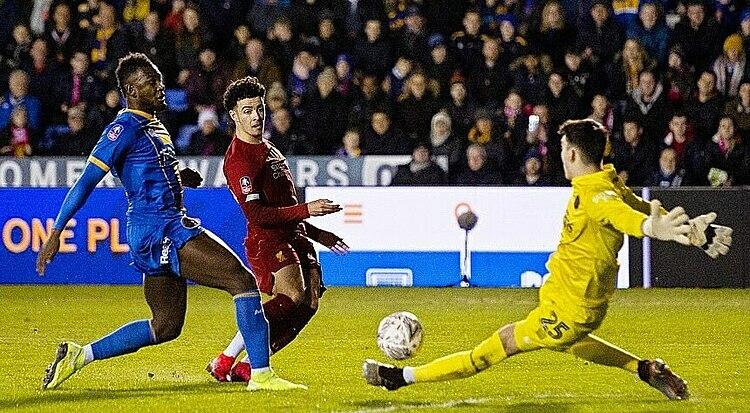 Jones (đỏ) dứt điểm thành bàn mở tỷ số cho Liverpool. Ảnh: Reuters.