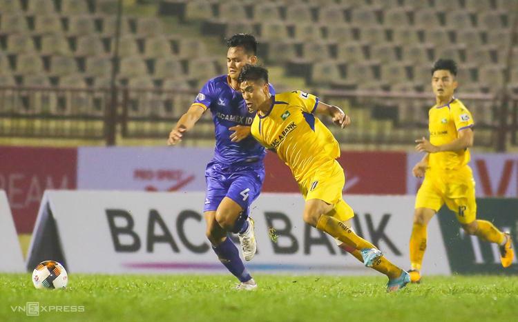 Phan Văn Đức tranh chấp với Hồ Tấn Tài trong trận đấu trên sân Vinh ngày 14/3. Ảnh: Xuân Thuỷ