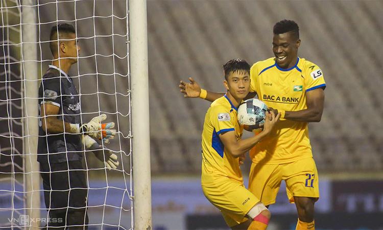 Văn Đức (áo vàng, trái) mừng bàn thắng vào lưới Bình Dương trên sân Vinh chiều 14/3. Ảnh: Xuân Thuỷ.
