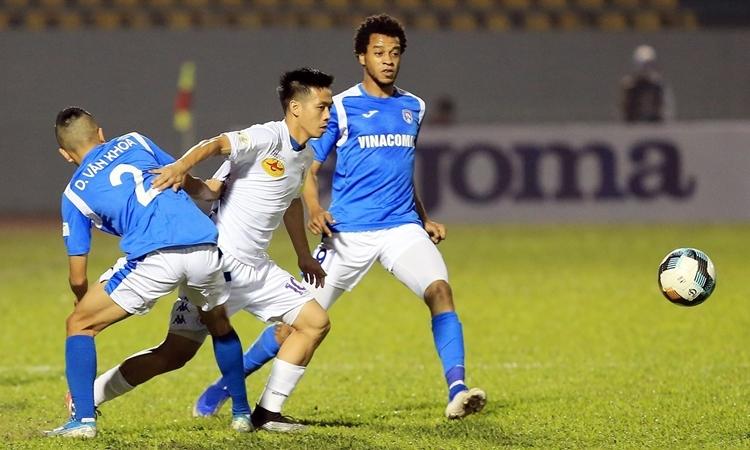Văn Quyết (áo trắng) trong vòng vây hai cầu thủ Quảng Ninh. Ảnh: VC.