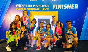 Runner chạy đêm xếp hàng check-in với bảng Finisher